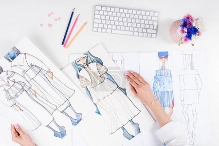 Photo pour Vue partielle de créatrice de mode féminine travaillant avec des croquis sur le lieu de travail - image libre de droit