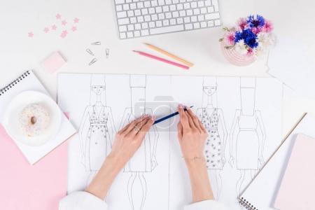 Photo pour Plan recadré de jeune créatrice de mode tenant crayon tout en travaillant avec des croquis - image libre de droit