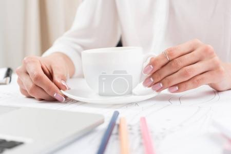 Photo for Close-up view of female hands holding cup of coffee at desk - Royalty Free Image