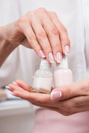 woman holding nail polishes