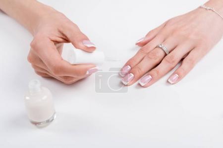 Photo pour Photo recadrée de femme tenant le vernis à ongles tout en faisant de manucure - image libre de droit