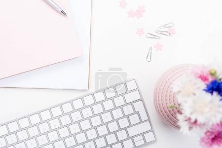 Photo pour Vue de dessus du clavier, ordinateur portable avec stylet, de fleurs et de bureau fournitures sur lieu de travail - image libre de droit