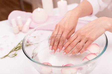 Photo pour Vue rapprochée des mains féminines reçoit actuellement des soins spa bol en verre avec pétales de roses - image libre de droit