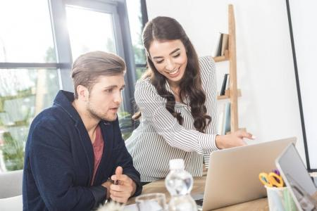 Photo for Portrait of multicultural young business people using laptop while working together in office - Royalty Free Image