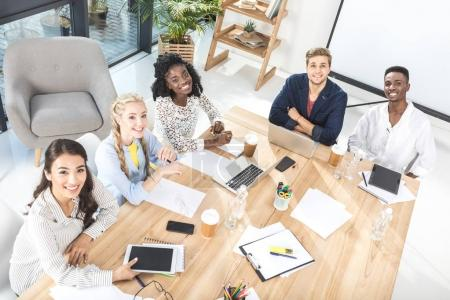 Photo for High angle view of multicultural group of business people looking at camera while sitting at table in conference room - Royalty Free Image