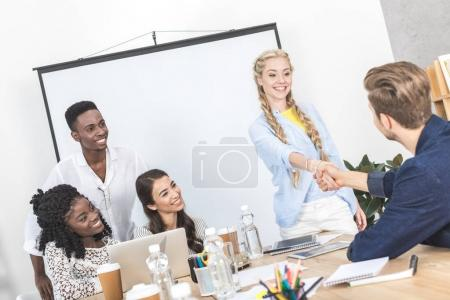 Photo for Smiling business partners shaking hands during conference with multicultural colleagues in office - Royalty Free Image