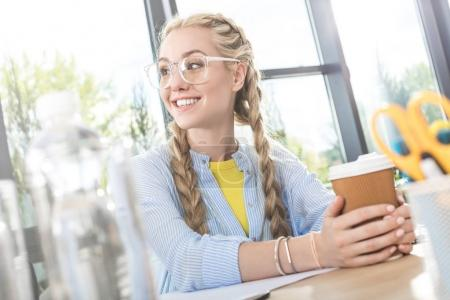 Photo for Portrait of smiling businesswoman in eyeglasses with coffee to go in hands sitting at table in office - Royalty Free Image