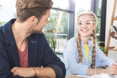 Photo pour Portrait de sourire des collègues de travail ayant la conversation tout en restant assis à table dans le Bureau - image libre de droit