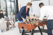 multicultural businessmen playing table football