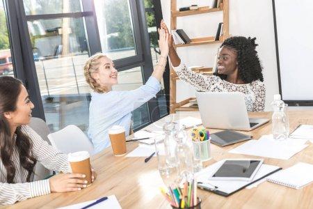 multicultural businesswomen giving high five