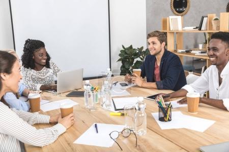 Photo pour Multicultural businesspeople souriant discuter stratégie commerciale au cours du séminaire au bureau - image libre de droit