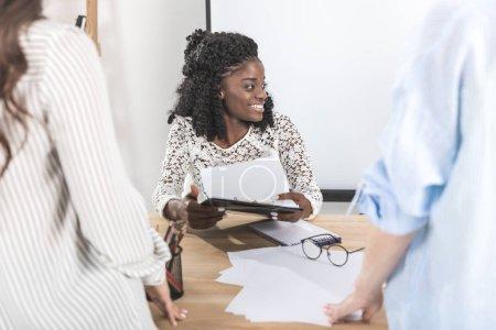 Photo pour Portrait d'une femme d'affaires afro-américaine joyeuse lors d'une réunion d'affaires avec des collègues au bureau - image libre de droit