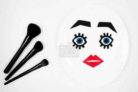 Photo for Makeup brushes and paper face with makeup on plate isolated on white, beauty concept - Royalty Free Image