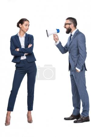 Photo for Handsome aggressive businessman with megaphone screaming on his female coworker, isolated on white - Royalty Free Image