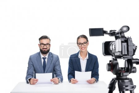 newscasters sitting in front of camera