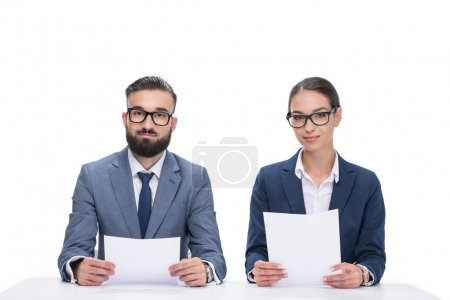 two newscasters with papers