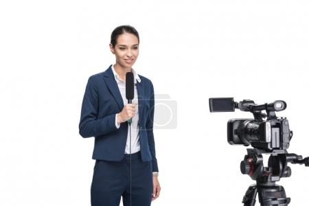 journalist with microphone looking at camera