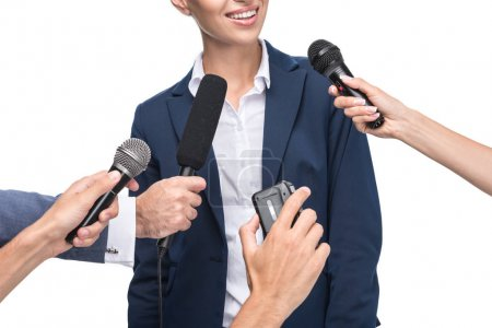 journalists with microphones interviewing businesswoman