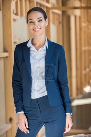 Photo pour Attrayante femme souriante posant en costume et en regardant la caméra - image libre de droit