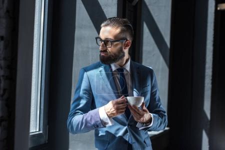 Photo pour Bel homme d'affaires barbu en costume gris buvant du café - image libre de droit