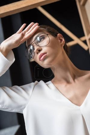 Photo for Thoughtful stylish businesswoman posing in white blouse and eyeglasses - Royalty Free Image