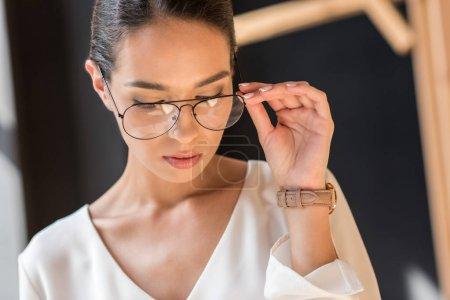 Photo pour Portrait d'attrayant élégant femme d'affaires posant en chemisier blanc et lunettes regardant vers le bas - image libre de droit