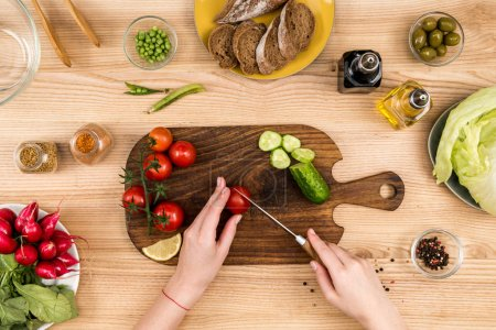 Photo for Partial view of woman cutting cherry tomatoes on wooden cutting board for salad - Royalty Free Image