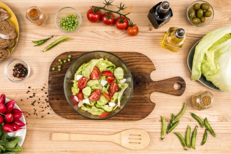 Photo for Top view of fresh homemade summertime salad in bowl and wooden spoon on tabletop - Royalty Free Image