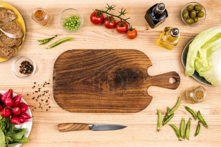 Photo for Top view of empty wooden cutting board, knife and fresh vegetables on tabletop - Royalty Free Image