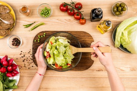 Photo for Cropped shot of woman preparing fresh vegetables salad at home - Royalty Free Image