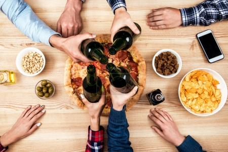 Photo for Partial view of friends clinking bottles of beer together while having pizza on dinner - Royalty Free Image