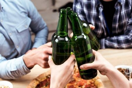Photo for Close up view of friends clinking bottles of beer together while having pizza on dinner - Royalty Free Image