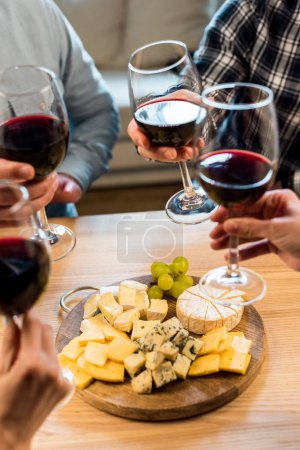 friends eating cheese and drinking wine