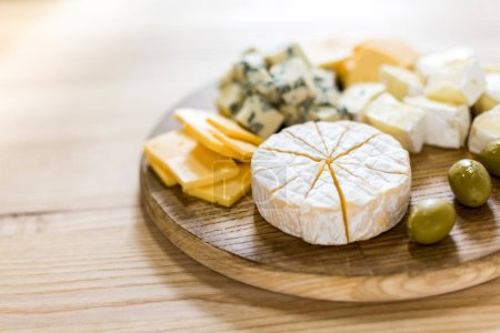 Photo for Close up view of various fresh cheese slices and pieces with olives on wooden board - Royalty Free Image