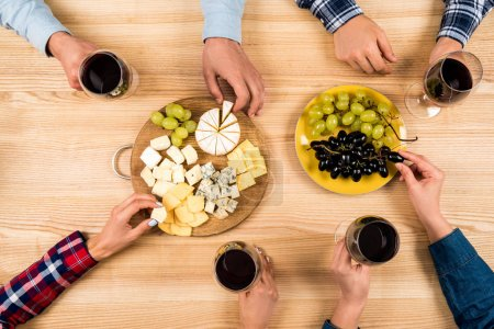 Photo for Top view of friends eating cheese with grapes and drinking wine at home - Royalty Free Image