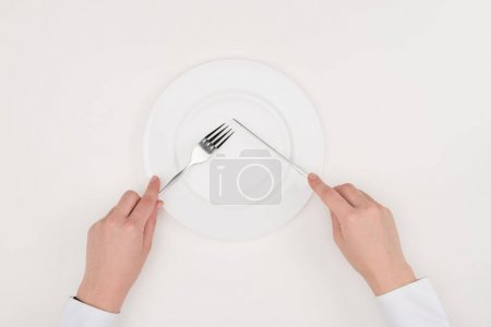 Photo for Top view of hands, empty plate and cutlery isolated on white - Royalty Free Image