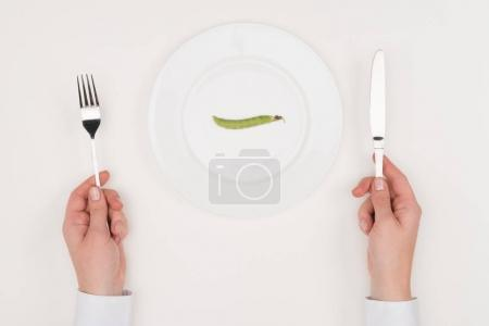 Hands, cutlery and pea on plate