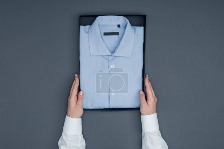 Photo for Cropped shot of tailor holding box with cotton shirt isolated on grey - Royalty Free Image