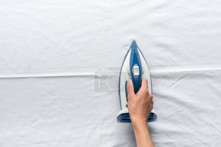 Photo for Partial view of man ironing white bed sheets - Royalty Free Image
