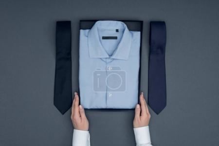 Photo for Cropped shot of tailor holding box with shirt and neckties arranged near by isolated on grey - Royalty Free Image