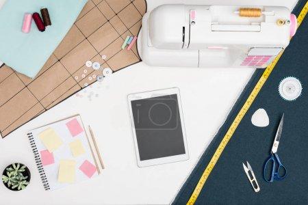 Photo pour Pose plate avec tablette numérique avec écran blanc, machine à coudre, feuille de coupe et autres équipements de couture isolés sur blanc - image libre de droit