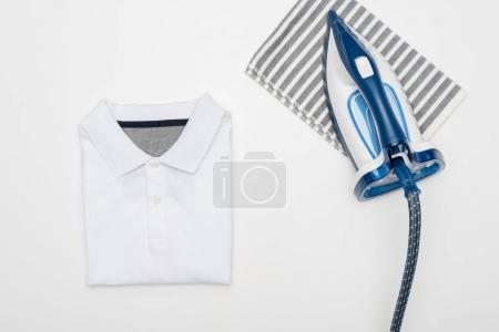 Photo for Top view of electric iron, textile and clothing isolated on white - Royalty Free Image