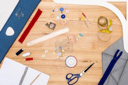 Photo pour Vue de dessus des broches, ciseaux, textiles et fermetures éclair sur table en bois - image libre de droit