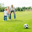 Father with kids playing soccer in park