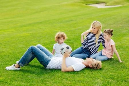 Photo for Happy young family with soccer ball resting on green grass in park - Royalty Free Image