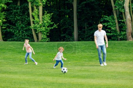 Photo for Happy young father with two adorable children playing soccer on green lawn at park - Royalty Free Image