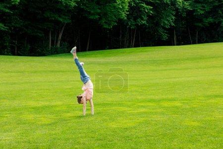 girl performing handstand in park
