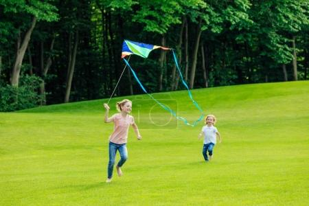 Photo for Adorable happy brother and sister playing with kite on green meadow in park - Royalty Free Image