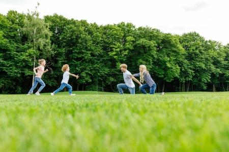 Photo for Happy young family with two kids playing on green meadow in park - Royalty Free Image