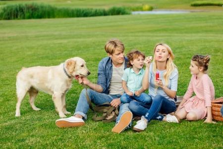 Familie mit Hund ruht auf Gras